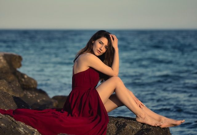 woman wearing a red tunic dress by the sea