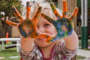 Young girl with paint in her hands